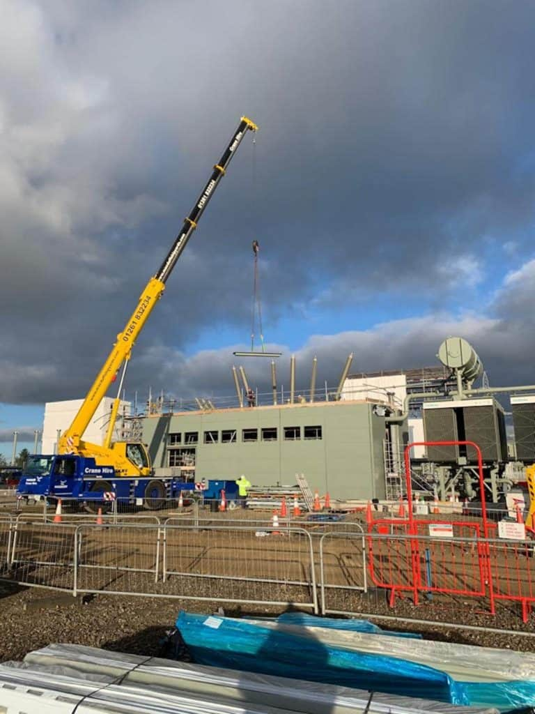 Cranes on site lifting panels into place for fixing
